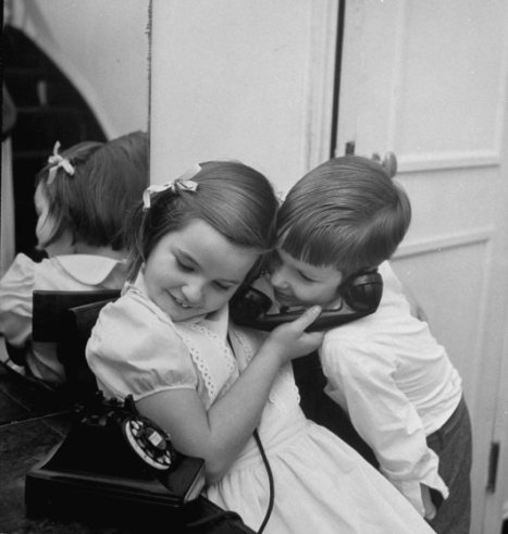 Brother and sister sharing the telephone